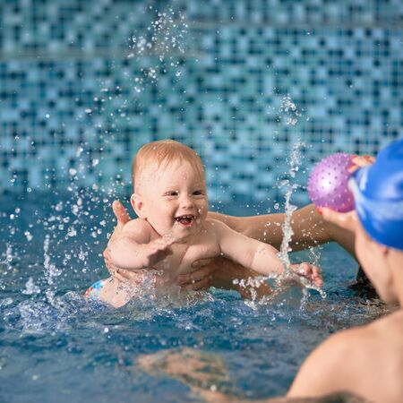 Adorable cheerful child is splashing in blue water smiling and trying to reach for his ball in his moms hands, cropped hands helping him to float Archivio Fotografico