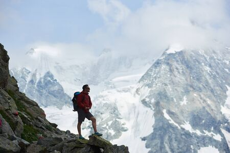 Side view of tourist with backpack standing on big stone, looking at beautiful mountains with snow. Trekking, mountain hiking, man reaching peak. Wild nature with amazing views. Sport tourism in Alps.