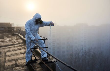 Researcher wearing protective outfit is conducting the study, using blue reagent in glass flask on top of high building over sunrise. Concept of environmental problem Archivio Fotografico