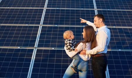 Back view of a beautiful young family, standing together holding a baby near photovoltaic solar panel on a sunny day, copy space, modern family concept 免版税图像
