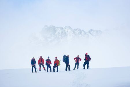Hikers team standing on hillside valley covered with snow. Male alpinists and trekking sticks enjoying the view of winter mountains while taking rest break during hike, looking to the camera Stock Photo