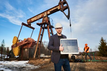 Portrait of businessman in suit jacket, helmet, holding mini solar module, showing thumb up. Oil operator working with pump jack on territory of oil field on background. Concept of alternative energy