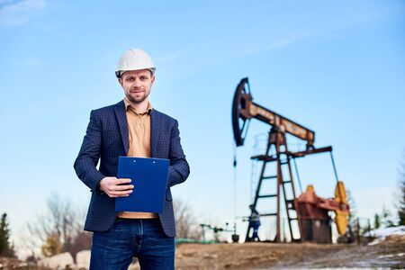 Portrait of engineer wearing suit jacket and white helmet, holding folder and making some notes, oil worker working with oil pump jack and blue sky on background. Concept of oil extraction 版權商用圖片