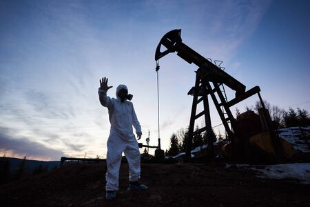 Silhouette of male scientist showing stop sign while standing on territory of oil field with pump jack and beautiful sky on background. Environmentalist wearing white radiation suit, gas mask, gloves