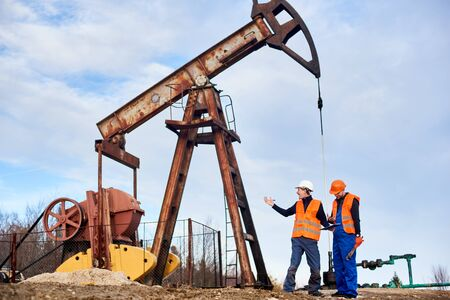 Two oil engineers wearing overalls, orange vests, and helmets, standing on an oilfield next to oil pump jack discussing something on a sunny day. Concept of petroleum industry and oil extraction. Фото со стока