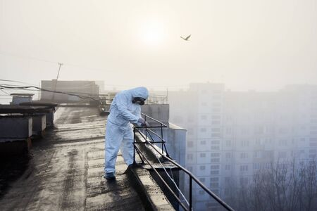 Laboratory worker on the roof conducting tests on subject of air pollution, sun is rising up and light is flooding the territory, copy space