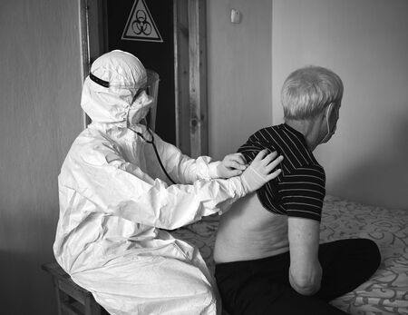 Black and white snapshot of a doctors examination at patients home during quarantine 2020. Doctor in protective suit and gloves checking infected old male patient. Biohazard sign hanging on door Standard-Bild