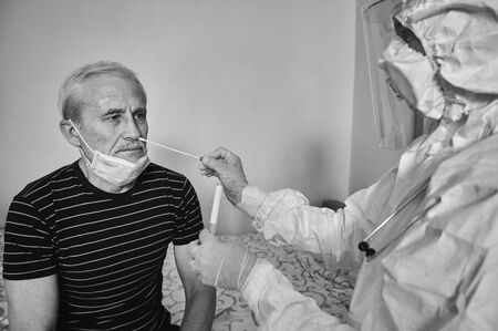 Black and white cropped snapshot of doctors visit at home. Nurse taking coronavirus test analysis with medical swab to old mans nose. Test tube for taking OP NP patient specimen sample. Stock Photo