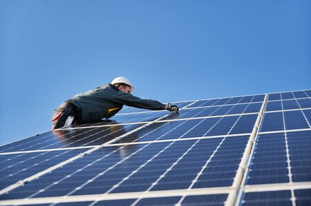 Male worker mounting solar modules, panels and support structures of photovoltaic solar array. Electrician wearing safety helmet and gloves. Concept of sun energy and power sustainable resources. Banque d'images