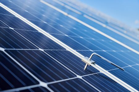Close-up snapshot of a new blue shiny solar module and a hex key stuck in between. Green energy concept. Modern technologies, ecological solution, power sustainable resources concept