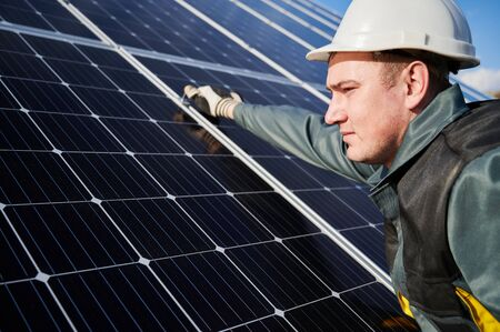 Close up of male worker, wearing protective suit, helmet and gloves. Electrician installing a photovoltaic solar batteries on sunny day. Concept of alternative energy and power sustainable resources. 写真素材