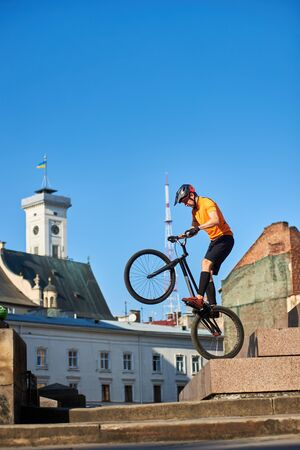 Side view of a cyclist standing on a black bike. Focused athlete preparing doing trick in city. Athlete holding a mountain bike and standing on one wheel. Concept of keeping balance. Фото со стока