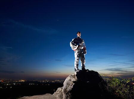 Brave astronaut standing on top of rocky hill with beautiful blue sky on background. Handsome spaceman in white space suit holding helmet. Concept of cosmonautics and space travel.