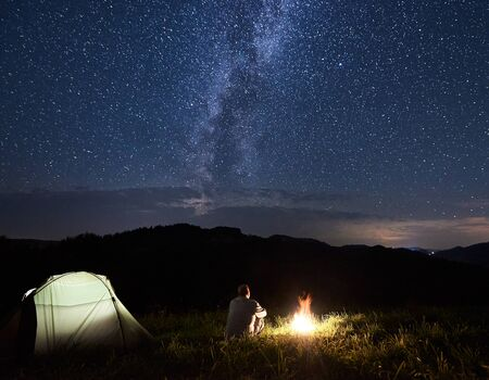Tourist is relaxing near bonfire enjoying the silhouettes of mountains under starry sky with bright milky way. Night camping in mountains. Powerful mountains under a magnificent sky with bright stars