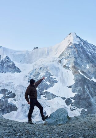 Side view snapshot of a tourist pointing on one of the most beautiful mountains in Swiss Alps - Ober Gabelhorn, which one side is covered with snow. Nature with amazing views. Sport tourism in Alps.