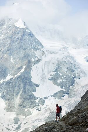 Incredibly beautiful mount in Swiss Alps - Ober Gabelhorn, male hiker with backpack standing on a slope enjoying a cold quiete scenery. Concept of freedom, mountain hiking, tourism and alpinism