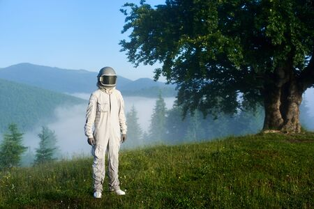 Portrait of a spaceman wearing white space suit and a helmet standing on a green mountain meadow on a hill, big old tree and fantastic foggy spruce forest in a valley on background. Travel concept