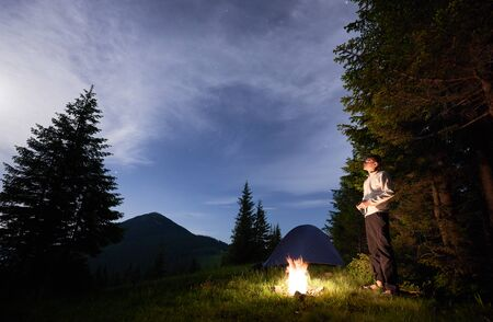 Young man standing by a burning fire under the evening sky with manifesting stars on the background of camping in the mountains near the pines. Active lifestyle concept 版權商用圖片