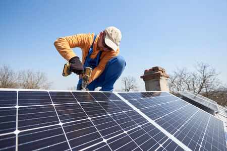 Male engineer installing stand-alone solar photovoltaic panel system using screwdriver. Electrician mounting blue solar module on roof of modern house. Alternative energy sustainable resources concept Фото со стока