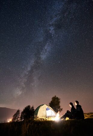 Back view of happy couple travellers sitting at bonfire beside camp and glowing tourist tent under night sky full of stars and Milky way. On background amazing starry sky, mountains and luminous city Banque d'images