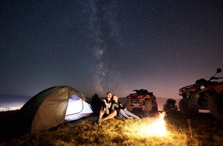 Man and woman sitting together near tourist tent, burning campfire, two atv quad motorbikes on the top of mountain, romantic couple enjoying beautiful view of night sky full of stars and Milky way