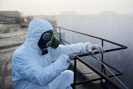 Scientist is working with a railing on the roof in the morning, wearing protective outfit and gas mask, close-up snapshot Archivio Fotografico