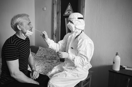 Black and white snapshot of a doctors examination at home. Nurse taking coronavirus test analysis with medical swab to old mans nose. Test tube for taking OP NP patient specimen sample