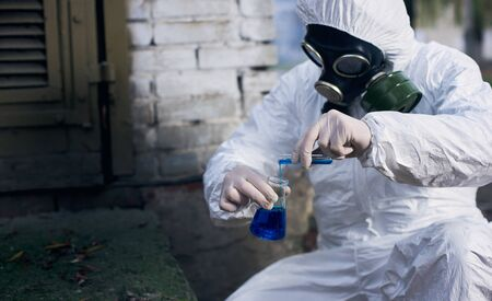 Ecologist in protective suit, gas mask and gloves. Scientist making expertise using glass flasks and local samples.