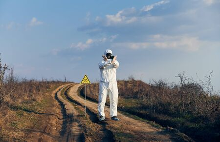Scientist in radiation suit and gas mask showing that entrance on territory is forbidden, standing near yellow triangle with skull and crossbones sign and warning about poisonous substances and danger
