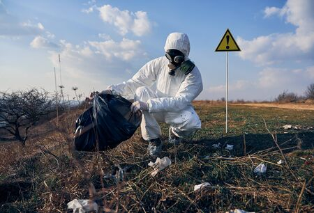 Ecologist wearing white protective coverall, gas mask, crouching collects plastic garbage into black waste bag outdoors, caution sign behind him. Concept of ecology, environmental pollution 版權商用圖片