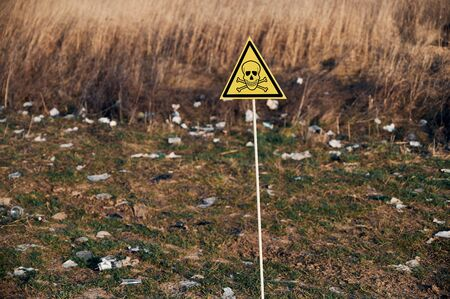 Yellow triangle with skull and crossbones symbol warning about poisonous substances and danger on abandoned territory with trash. Garbage waste field with toxic hazard sign 版權商用圖片
