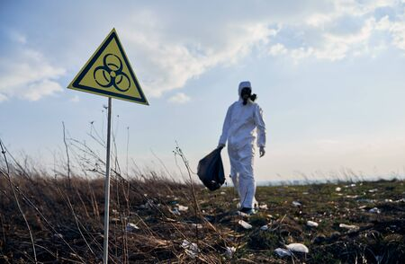 Focus on biohazard warning sign. On blurred background ecologist in suit and gas mask holding garbage bag, standing on abandoned territory with trash. Concept of ecology, environmental pollution Banque d'images