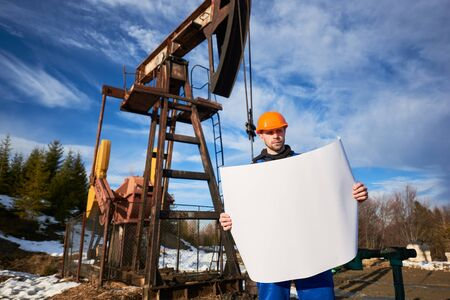 Portrait of an oil worker in a blue uniform and orange helmet standing in an oilfield with a printed plan on a beautiful sunny day, oil pump jack and blue sky on background