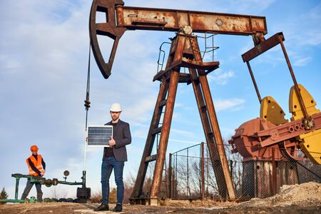 Portrait of smiling businessman in suit jacket, white helmet, holding mini solar panel, showing thumb up. Oil operator working with pump jack on oil field on background. Concept of alternative energy
