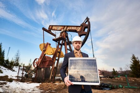 Businessman wearing a sport coat, jeans and a white helmet, holds mini solar module, standing in an oil field next to an oil pump jack. Concept of petroleum industry and alternative source of energy 版權商用圖片