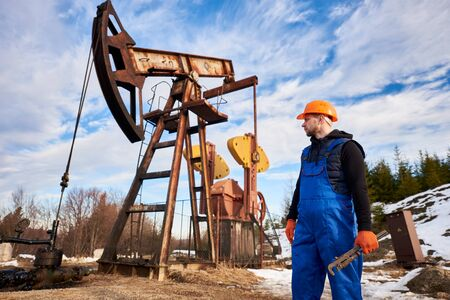 Horizontal snapshot of oil worker in orange helmet during his working day in an oilfield, oil engineer holding a pipe wrench looking at a pump jack behind him. Concept of oil and gas industry