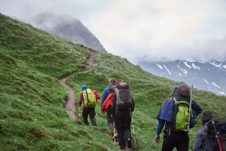 Back view of travelers with backpacks using trekking poles while climbing the grassy hill. Group of male hikers walking on path and heading to foggy mountain. Concept of hiking, climbing and alpinism. Imagens