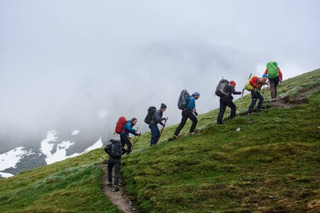 Group of male hikers with backpacks using trekking sticks while climbing grassy hill. People walking uphill in mountains with foggy cliff on background. Concept of hiking, travelling and backpacking.