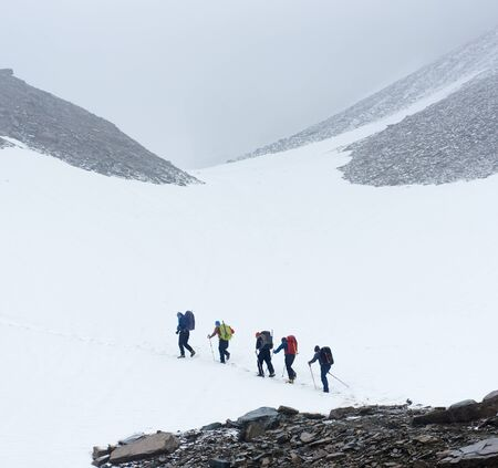 Group of male hikers with backpacks and trekking sticks walking long distance in winter mountains, hiking on ice field in mountainous region. Concept of travelling, hiking and winter mountain tourism.