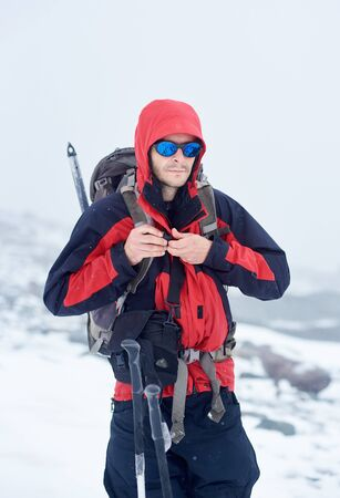 Male tourist in sunglasses fastening travel backpack and looking at camera. Hiker with shoulder bag wearing sport winter jacket with hood and stylish shades. Concept of travelling, hiking and alpinism Imagens