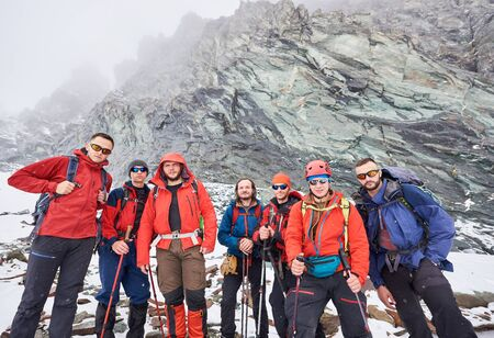 Travelers team in winter jackets and hiking sunglasses posing near huge rocky mountain. Group of backpackers with trekking sticks looking at camera. Concept of travelling, hiking and mountaineering.