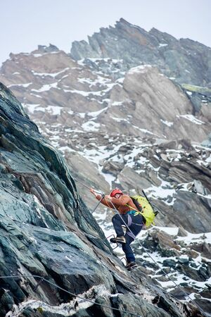 Side view alpinist with backpack using fixed rope to climb high rocky mountain. Man climber ascending alpine ridge and trying to reach mountaintop. Concept of mountaineering and alpine rock climbing.