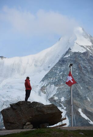 Male tourist looking at beautiful mountains scenery . Man standing on stones near the flagpole with Switzerland flag. Ober Gabelhorn is on background. Wild nature with amazing views. Tourism in Alps. 版權商用圖片