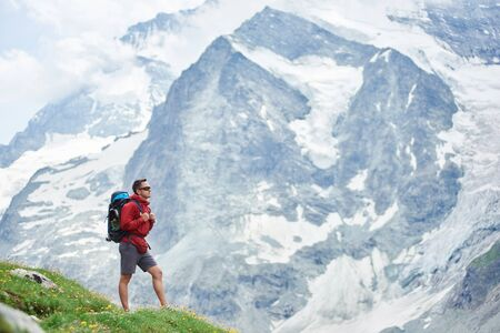 Horizontal snapshot of a huge snowy mountain in Swiss Alps which takes all the background, male hiker with a backpack standing on green meadow on foreground. Concept of tourism, hiking, trekking. 版權商用圖片