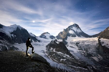 Horizontal snapshot of incredible blue sky full of stars and the Moon over cool eternal snowy peaks of Pennine Alps in Switzerland, a tourist standing and watching the beauty Dent Blanche