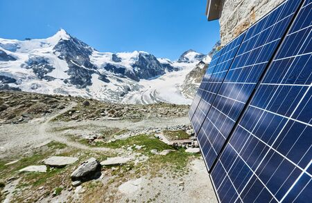 Close-up perspective snapshot of solar modules installed on the walls of alpine hut in Swiss Alps as alternative source of energy, concept of green ecology