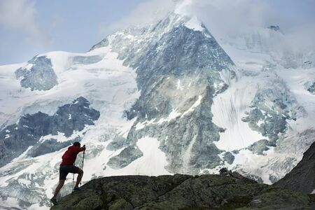 Horizontal snapshot of amazing, rocky mountain Ober Gabelhorn in snow in the Pennine Alps in Switzerland, male tourist climbing with hiking poles on foreground