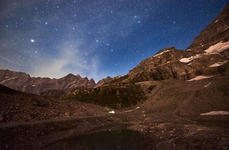 Fantastic view of blue night sky with stars over rocky hills, mountain ridges. Magnificent night mountain landscape with small lake, camp tents. Concept of travelling, mountainous region, nighttime. 版權商用圖片