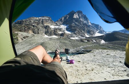 View from tourist tent on mountain lake, Matterhorn. Male legs of incognito tourist enjoying the view of beautiful rocky hills in sunny summer day. Concept of tourism, camping, nature beauty.