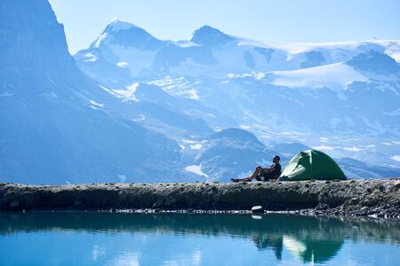 Man traveller enjoying scenery, sitting in chair near tent, admiring fantastic view of alpine mountains near lake with fresh clear water. Concept of travelling, hiking and camping in Alps. 版權商用圖片